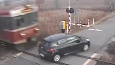 Das Auto überquert den Bahnübergang. Doch dann kommt der Zug angerast!