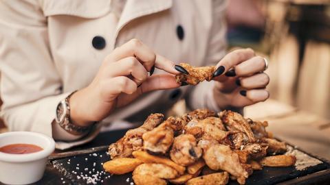Frau isst genüsslich Chicken Wings, dann bekommt sie einen Schock, als sie das sieht