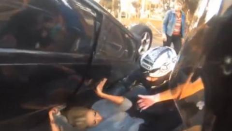 Diese Frau hatte das Glück, dass dieser Motorradfahrer vorbeikam, als sie unter ihrem Auto eingeklemmt war