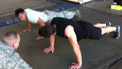 Ein Fitnessspezialist fordert einen Soldaten zu einem Liegestütz-Wettbewerb heraus