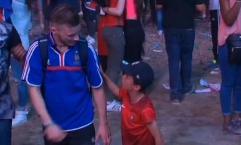 Ein kleiner Junge und Anhänger Portugals tröstet einen französischen Fan