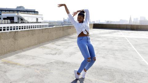 Junge Frau spaziert mit aufgemalter Jeans durch die Stadt