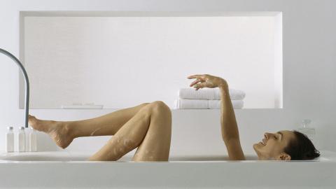 Frau entspannt in der Badewanne, doch dann bleibt sie stecken